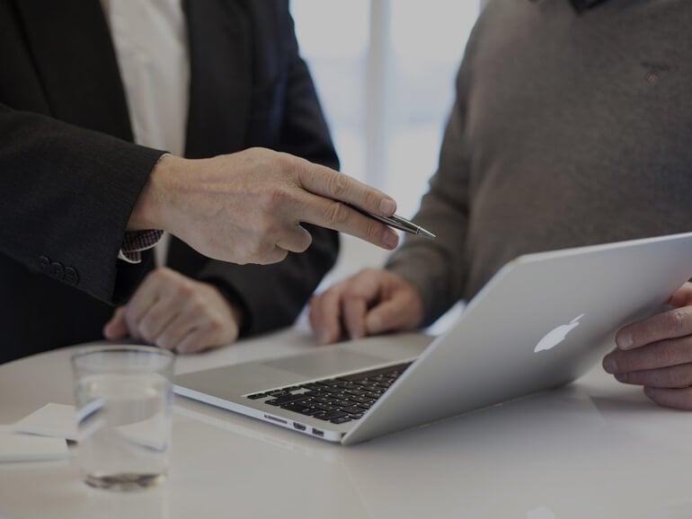 Deux hommes discutent devant un écran avec un stylo à la main