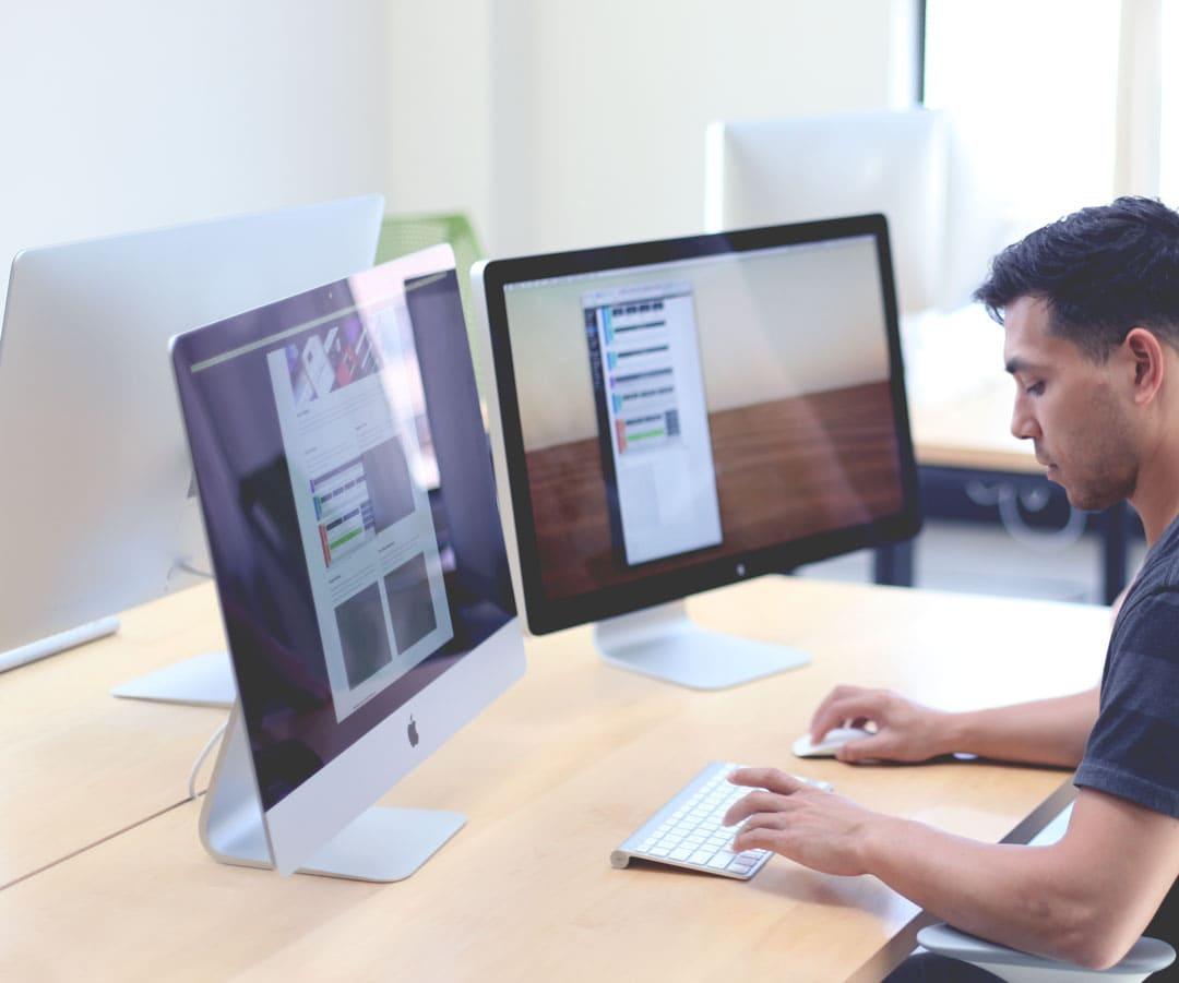 Homme en train de rédiger du texte devant son ordinateur