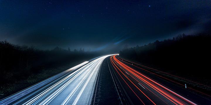 Autoute vue de nuit avec les feux des voitures laissant une traînée lumineuse.