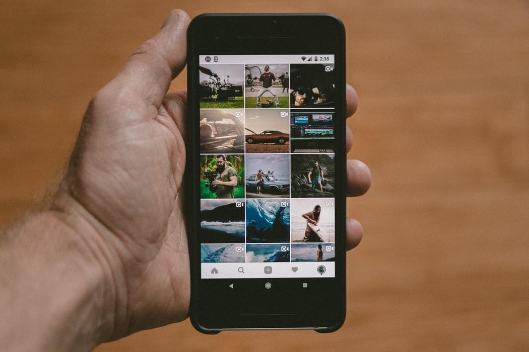 Main d'homme tenant un smartphone avec Instagram sur l'écran